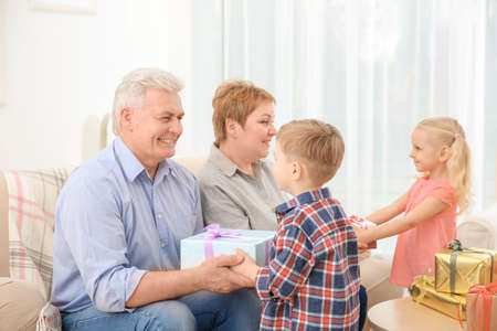 Happy senior couple and their grandchildren exchanging gifts at home Stock Photo