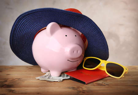 Pink piggy bank in straw hat with money, passport and sunglasses on wooden table Zdjęcie Seryjne