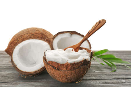Composition with coconut oil in shell on wooden table Foto de archivo