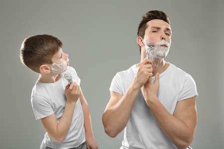 Father and son shaving on light background Фото со стока