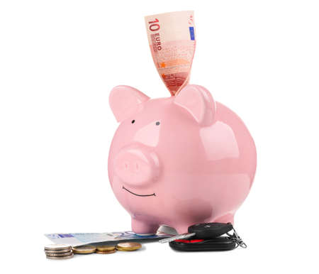 Piggy bank with money and key on white background