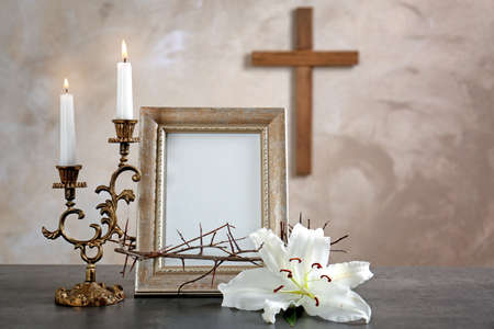 Photo frame, lily, crown of thorns, candles and cross on beige background
