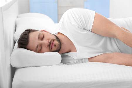 Joven acostado en la cama con almohada ortopédica en casa