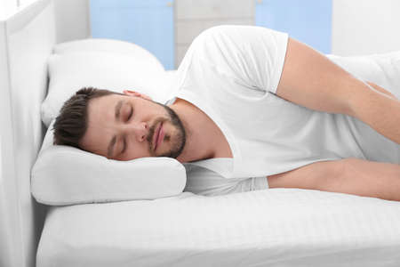 Young man lying on bed with orthopedic pillow at home Stock fotó