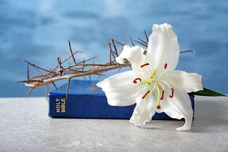 Santa Biblia, lirio y corona de espinas sobre fondo claro Foto de archivo