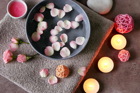Beautiful spa composition of flower petals with water in bowl and candles on gray background 免版税图像