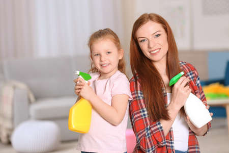 Little girl and her mother cleaning up at home