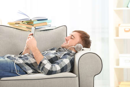Concept of audiobook. Handsome young man with headphones and phone lying on sofa at home