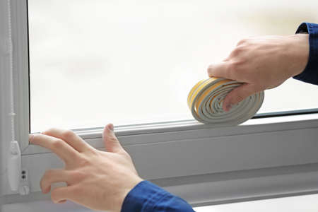 Hands of young worker applying rubber strip onto window in office