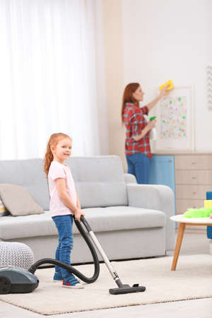 Little girl using vacuum cleaner while helping mother at home Stock Photo