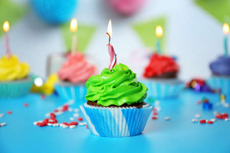 Delicious cupcake with lighted candle on festive background Stock Photo