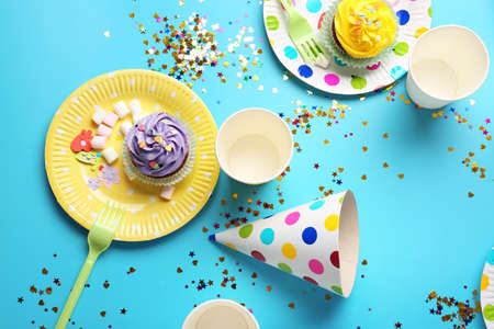 Plates with birthday cupcakes and paper glasses on table Foto de archivo