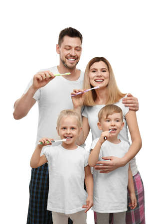 Young family with children brushing teeth on white background