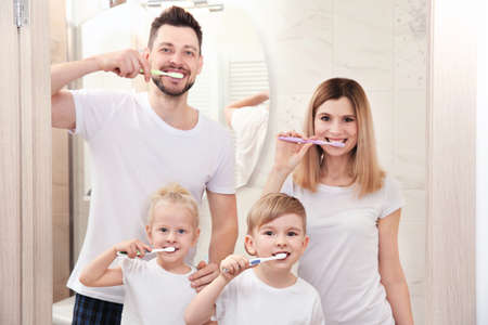 Young couple and their children brushing teeth in bathroom
