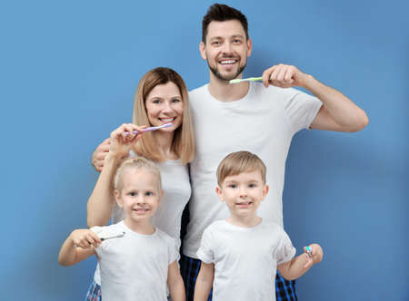 Young family brushing teeth on blue background