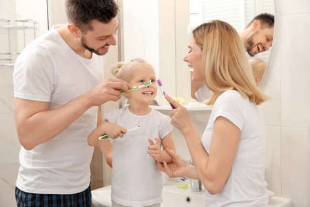 Young couple and their beautiful daughter brushing teeth near mirror in bathroom Stockfoto