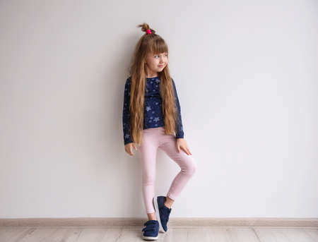 Little fashion girl posing in light room Foto de archivo