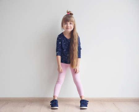 Little fashion girl posing in light room 스톡 콘텐츠