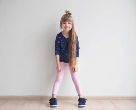 Little fashion girl posing in light room Standard-Bild