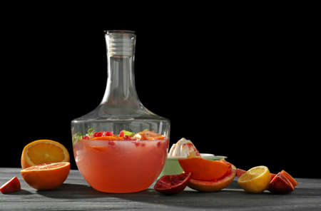 Decanter of fresh cocktail with pomegranate and orange on table