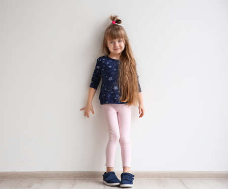 Little fashion girl posing in light room 스톡 콘텐츠