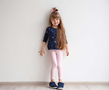 Little fashion girl posing in light room Foto de archivo