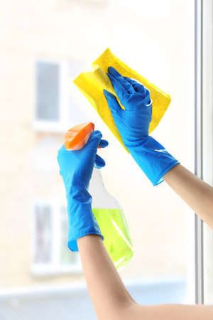 Female hands in gloves cleaning window, close up Stock Photo