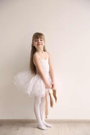 Beautiful little ballerina holding ballet shoes in light dance studio