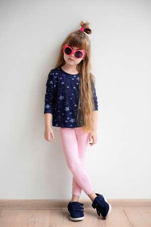 niña de moda posando en la habitación de luz