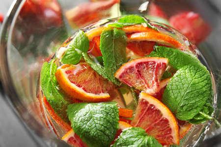 Glass jug with fresh citrus cocktail, closeup
