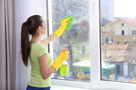 Young woman using detergent and rag while cleaning window in light room Stock Photo