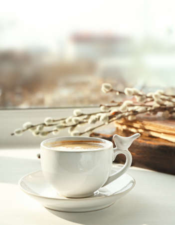 Ceramic cup with coffee on white window sill