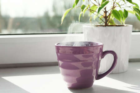 Cup of delicious hot drink on window sill