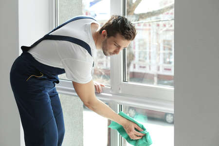 Young man cleaning window in office