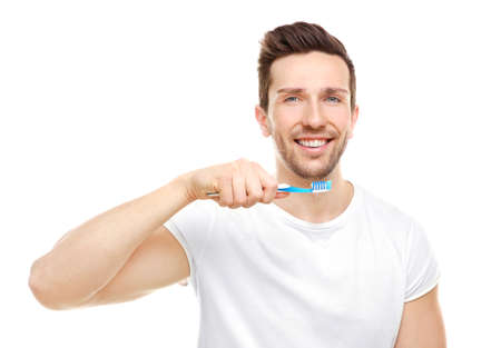 Young handsome man brushing teeth on white background Stock Photo