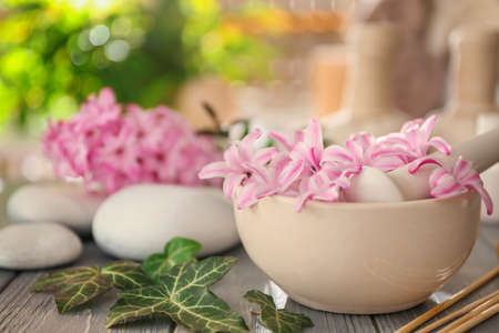 Beautiful spa composition with flowers in bowl on table Stock Photo