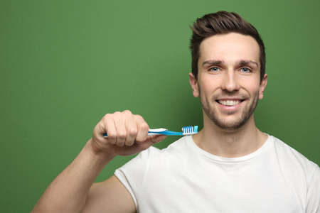 Young handsome man brushing teeth on color background