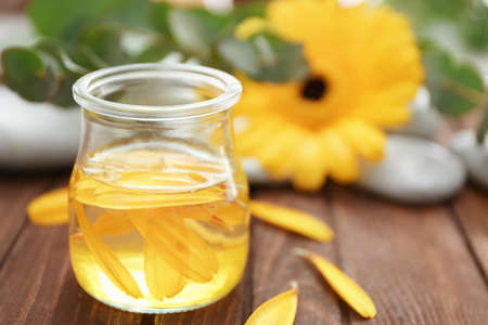 Beautiful spa composition with flower petals in glass jar on table