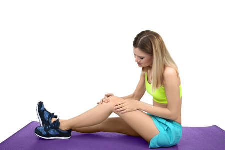 Young sporty woman suffering from pain in knee on white background