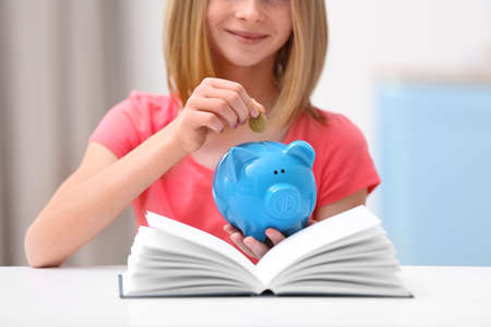 Cute girl putting coin into piggy bank at home, closeup Foto de archivo