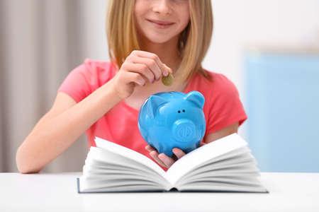 Linda chica poniendo monedas en hucha en casa, primer plano Foto de archivo - 98035660