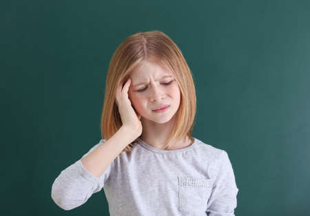 Cute girl suffering from headache on color background Stockfoto