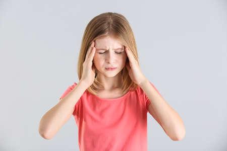 Cute girl suffering from headache on light background