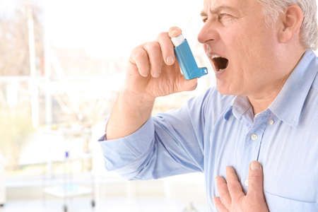 Elderly man using inhaler in clinic