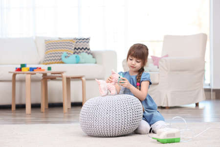 Cute little girl playing with nebulizer at home. Allergy concept