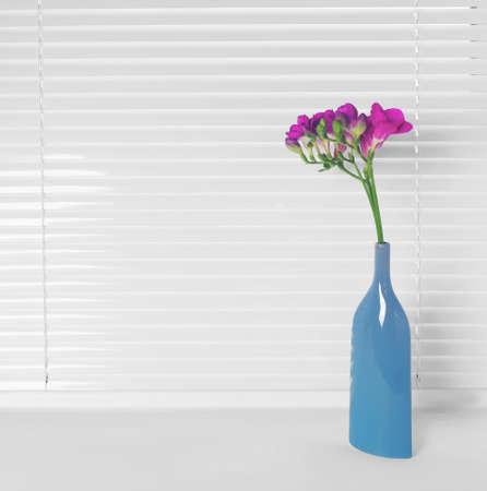Vase with beautiful flowers on windowsill