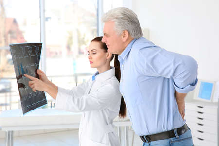 Female orthopedist examining senior man in clinic