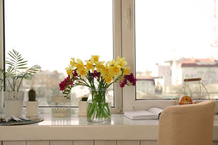 Vase with beautiful flowers on windowsill
