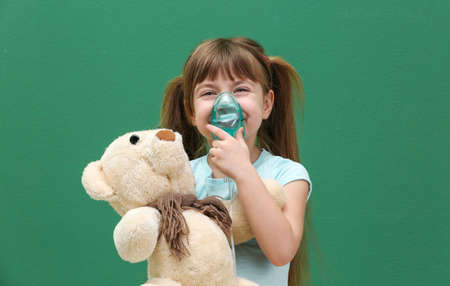 Cute little girl holding nebulizer and toy bear on color background. Allergy concept Stock Photo
