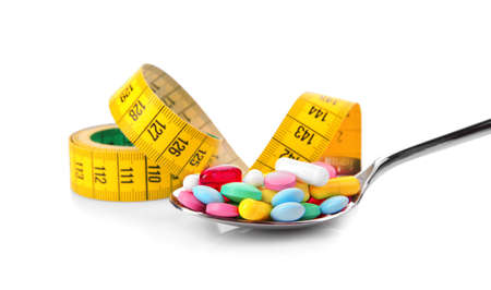 Diet concept. Measuring tape and spoon with pills on white background